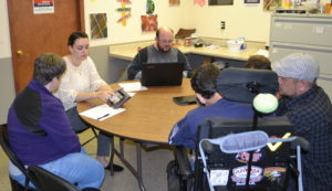 Project coordinator Sarah Roberts sits at a round table with four A.R.C. participants and one A.R.C. staff member. gets feedback from A.R.C. participants at the first interactive session on website accessibility at the Schoharie A.R.C.