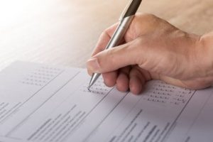 A hand holding a pen is shown filling out a survey or test